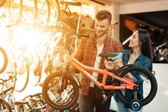 Un individuo joven y una muchacha están eligiendo una bicicleta del ` s de los niños Fotos de archivo libres de regalías