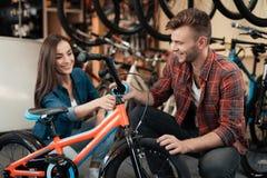 Un individuo joven y una muchacha están eligiendo una bicicleta del ` s de los niños Fotografía de archivo