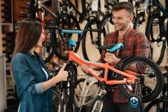 Un individuo joven y una muchacha están eligiendo una bicicleta del ` s de los niños Imágenes de archivo libres de regalías