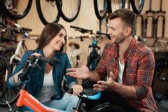 Un individuo joven y una muchacha están eligiendo una bicicleta del ` s de los niños Fotografía de archivo libre de regalías