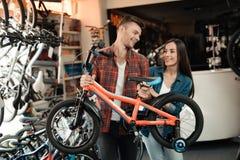 Un individuo joven y una muchacha están eligiendo una bicicleta del ` s de los niños Imagen de archivo