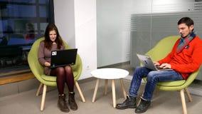 Un individuo joven y una muchacha se están sentando en el ordenador