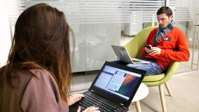 Un individuo joven y una muchacha se están sentando en el ordenador portátil metrajes