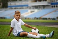 Un individuo lindo con un balón de fútbol que se sienta en una hierba verde y en un fondo del estadio Un futbolista en el aire li Fotos de archivo