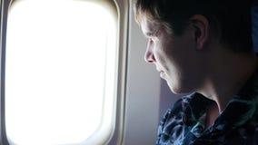 Un individuo mira hacia fuera la ventana de un avión en un día soleado metrajes