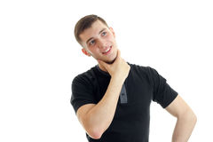 Un individuo pensativo joven en una camiseta negra y la mirada para arriba sonriente Fotografía de archivo