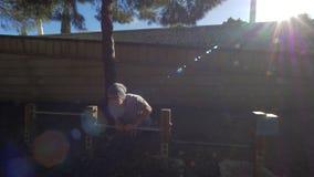 Un individuo que hace pectorales en una yarda soleada verde almacen de metraje de vídeo