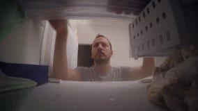 Un individuo que mira el congelador almacen de metraje de vídeo