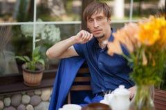 Un individuo que se sienta en un café que mira en la distancia Imagen de archivo libre de regalías
