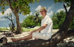 Un individuo que sienta en una conexión la playa maldives resto en la isla Fotografía de archivo