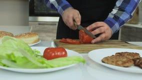 Un individuo regordete cocina las hamburguesas caseras en su cocina El hombre corta los tomates en la tabla de cortar Forma de vi almacen de video