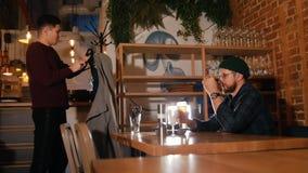 Un individuo saluda a su amigo en la barra y el individuo se sienta delante de él almacen de metraje de vídeo