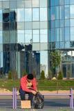 Un individuo sin hogar se sienta en el banco con una cartulina y una inscripción: dinero de la necesidad En el fondo es un centro Fotos de archivo