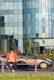Un individuo sin hogar se sienta en el banco con una cartulina y una inscripción: dinero de la necesidad En el fondo es un centro Foto de archivo