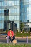Un individuo sin hogar se sienta en el banco con una cartulina y una inscripción: trabajo de la necesidad En el fondo es un centr Fotos de archivo libres de regalías