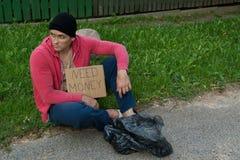 Un individuo sin hogar se sienta en la acera con una cartulina y una inscripción: dinero de la necesidad Fotos de archivo libres de regalías