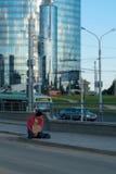 Un individuo sin hogar se sienta en la acera con una cartulina y una inscripción: dinero de la necesidad En el fondo es un centro Foto de archivo libre de regalías