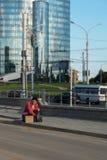 Un individuo sin hogar se sienta en la acera con una cartulina y una inscripción: trabajo de la necesidad En el fondo es un centr Imágenes de archivo libres de regalías