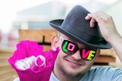 Un individuo sonriente joven en vidrios oscuros con el amor de la inscripción da un ramo de flores y saca su sombrero en el salud foto de archivo libre de regalías