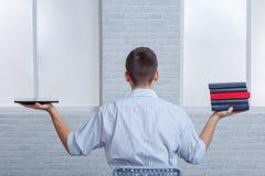 Un individuo sostiene un libro electrónico y un libro ordinario que los comparan Foto de archivo libre de regalías