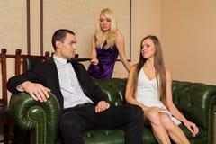 Un individuo y dos muchachas en el cuarto fotografía de archivo