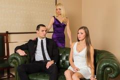 Un individuo y dos muchachas en el cuarto foto de archivo