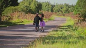 Un individuo y su novia están en una carretera nacional El marco en el foco largo Pares hermosos mismos en amor metrajes