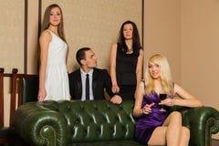 Un individuo y tres muchachas en el cuarto fotos de archivo