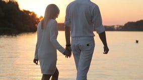 Un individuo y una muchacha están caminando a lo largo de la playa en la puesta del sol metrajes