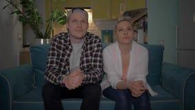 Un individuo y una muchacha que ven la TV el sentarse en el sofá en casa en el fondo de la cocina 4K metrajes