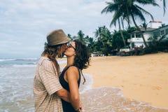 Un individuo y una muchacha se están besando en una playa Fotos de archivo