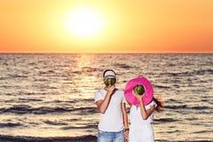 Un individuo y una muchacha se están colocando en la playa y están protegiendo sus cabezas con las sandías en sombreros imagen de archivo