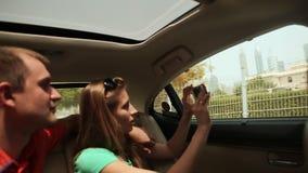 Un individuo y una muchacha viajan en Dubai en coche y admiran la ciudad almacen de metraje de vídeo