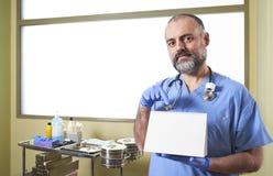 Un infermiere che tiene un cartello in bianco davanti ad un carretto di cura fotografie stock libere da diritti