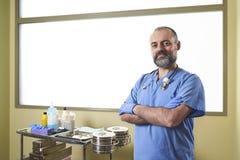 Un infermiere con i guanti blu del lattice davanti ad un carretto di cura immagine stock