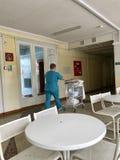 Un infermiere rotola un carretto con biancheria da letto lungo il corridoio dell'ospedale Immagine Stock Libera da Diritti