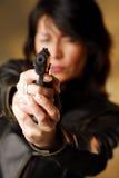Un infornamento della donna da una pistola Immagini Stock