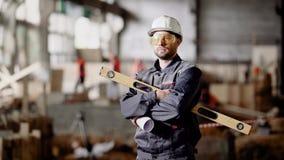 Un ingénieur adulte dans un casque tient dans des ses mains un niveau d'esprit pour mesurer le degré de déviation de la surface banque de vidéos
