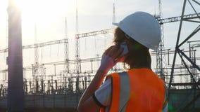 Un ingénieur de fille dans un casque blanc et un gilet protecteur orange inspecte une centrale avec des fils et l'électricité clips vidéos