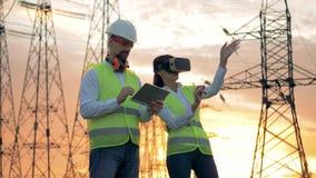Un ingénieur de mâle dactylographie sur un comprimé, alors qu'une femme porte des lunettes de VR 4K clips vidéos