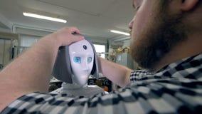 Un ingénieur place la perruque en plastique grise sur la tête de robots banque de vidéos