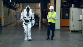 Un ingegnere e un robot stanno camminando lungo la fabbrica video d archivio
