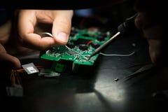 Un ingegnere sta lavorando ad un apparecchio elettronico Immagine Stock Libera da Diritti
