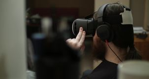 Un ingeniero barbudo joven utiliza los vidrios de la realidad virtual almacen de video