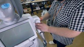 Un ingeniero cubre los brazos de los robots con la cubierta plástica del acabamiento blanco 4K almacen de metraje de vídeo