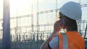 Un ingeniero de la muchacha en un casco blanco y un chaleco protector anaranjado examina una central eléctrica con los alambres y almacen de video