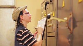 Un ingeniero de sexo femenino anota las lecturas de aparatos eléctricos en la centralita telefónica metrajes