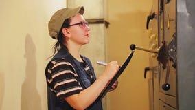 Un ingeniero de sexo femenino registra las lecturas de instrumento en el cuarto eléctrico metrajes