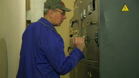 Un ingeniero del electricista enciende la electricidad en el panel almacen de video