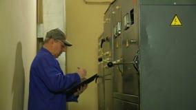 Un ingeniero del electricista enciende la electricidad en el panel y registra las lecturas de aparatos eléctricos almacen de metraje de vídeo